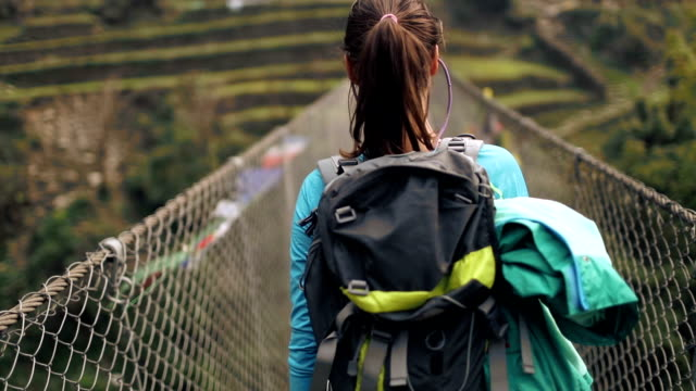 stockvideo's en b-roll-footage met wandelaar meisje oversteken van de brug - annapurna range
