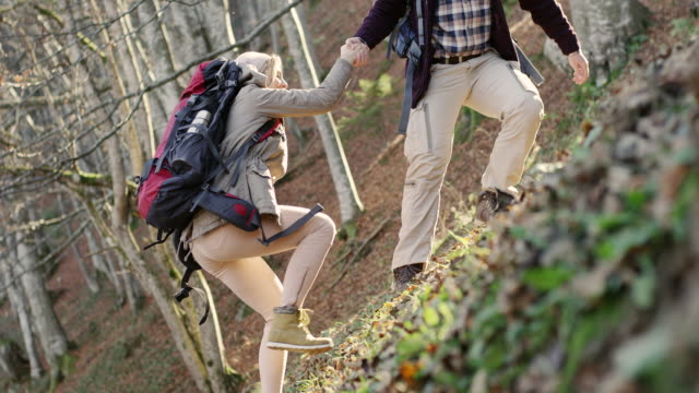 Hiker helping woman