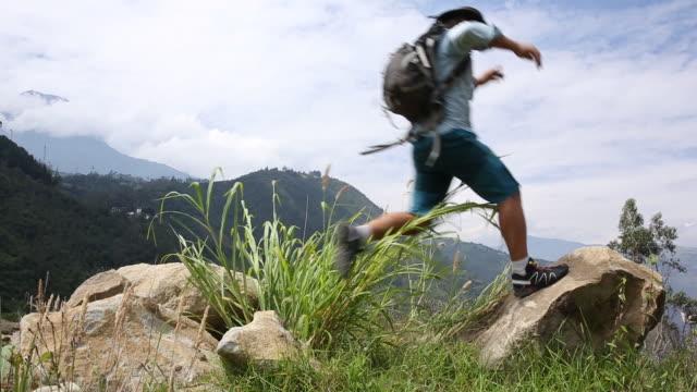 vidéos et rushes de hiker hops onto boulder above hills, mountain ranges - un seul homme d'âge mûr