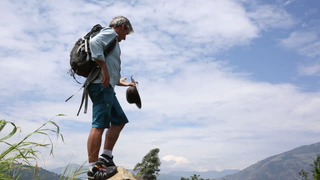 Hiker hops onto boulder above hills, mountain ranges
