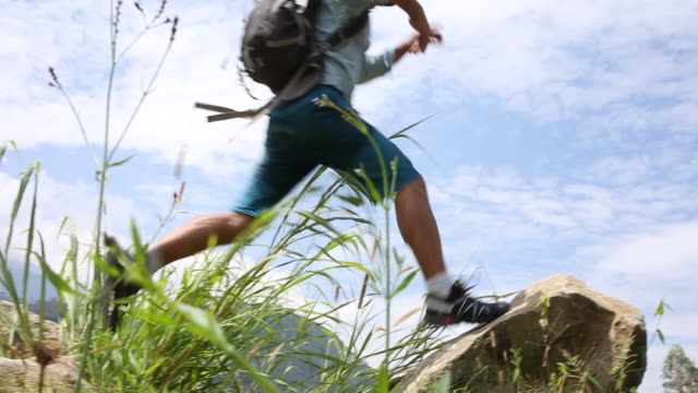 hiker hops onto boulder above hills, mountain ranges - one mature man only stock videos & royalty-free footage