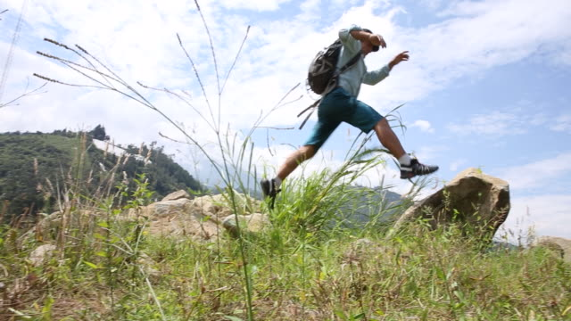 hiker hops onto boulder above hills, mountain ranges - only mature men stock videos & royalty-free footage