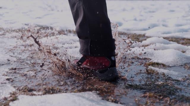 wanderer in stiefeln laufen, planschen im schnee und wasser, super slow motion - schlamm stock-videos und b-roll-filmmaterial