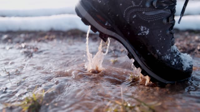 hiker in boots splashing in water on winter road, super slow motion - mud stock videos & royalty-free footage