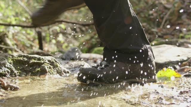 ms hiker in boots stepping,splashing in sunny stream - stivale video stock e b–roll