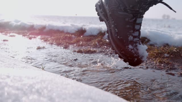 vídeos de stock e filmes b-roll de hiker in boots walking in snow and slush on winter road, super slow motion - passos