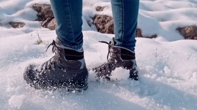 vídeos de stock e filmes b-roll de hiker in boots walking in snow, super slow motion - passos