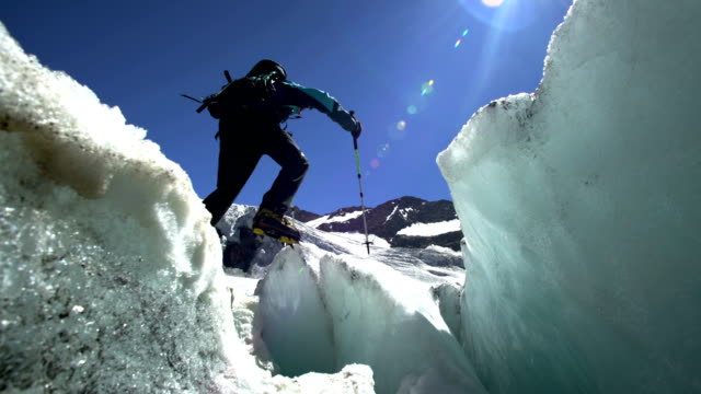 Hiker jumping a crack on the glacier on the top of the mountain