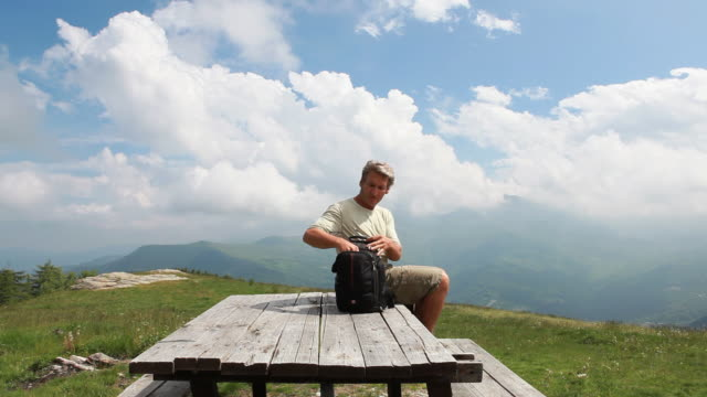 hiker jumps onto picnic table, uses digital tablet - rucksack stock videos and b-roll footage