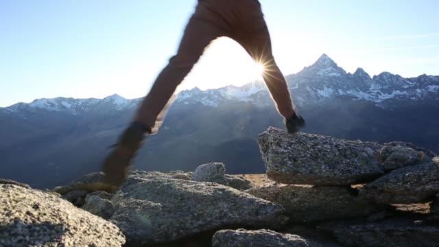 vídeos de stock e filmes b-roll de hiker leaps onto mountain summit, looks out to view - caminho adiante