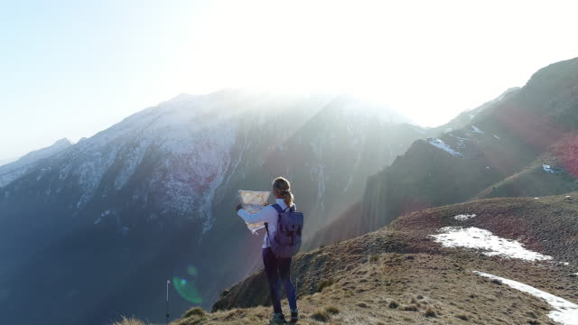 hiker looking at map from mountain top - alpinismo video stock e b–roll
