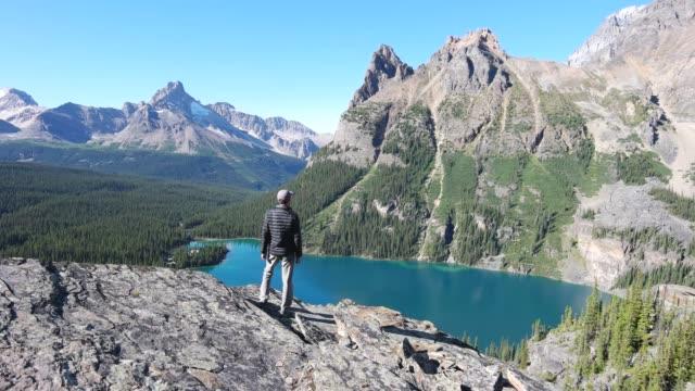 wanderer blickt auf bergblick im kanadischen rockies lake o'hara - kanada stock-videos und b-roll-filmmaterial