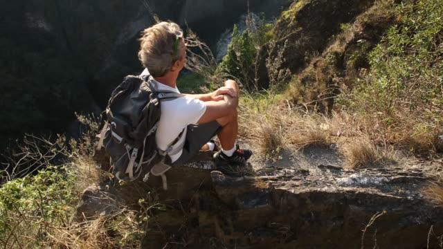 vidéos et rushes de hiker looks down into mountain canyon, takes pic - un seul homme d'âge mûr