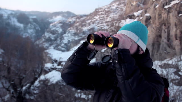 hiker looks through binoculars,winter landscape - canocchiale video stock e b–roll