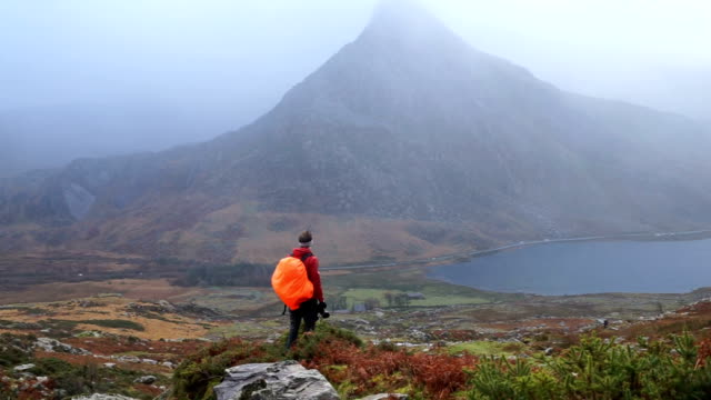 hiker makes his way through rugged highland environment admiring the views - snowdonia stock videos & royalty-free footage