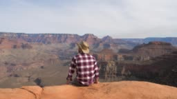 A Hiker Man Sits, Watching A Breathtaking View Of Grand Canyon Alone