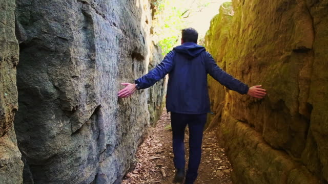 hiker man walking inside a wall crack, a wild and beautiful place, with nice corridor in the garrotxa region of catalonia. - narrow stock videos & royalty-free footage