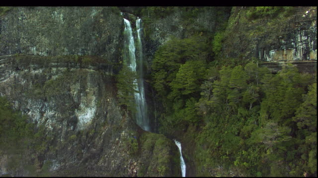 a hiker maneuvers at the base of a waterfall. - falling water stock videos & royalty-free footage