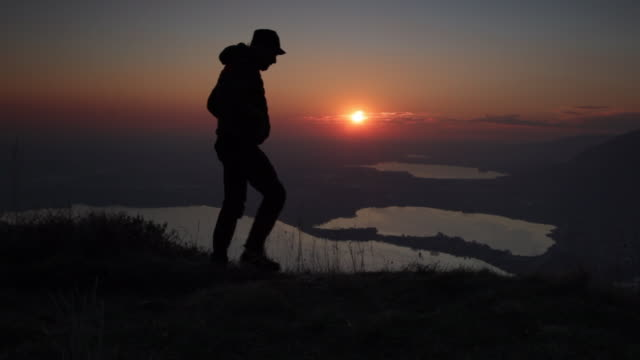 hiker on top of the mountain joining at sunset moment - orizzonte video stock e b–roll