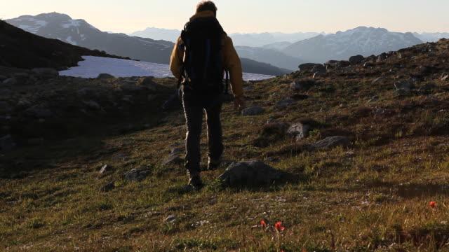 hiker passes overhead camera, walks to horizon, raises arms, mtns - hand an der hüfte stock-videos und b-roll-filmmaterial