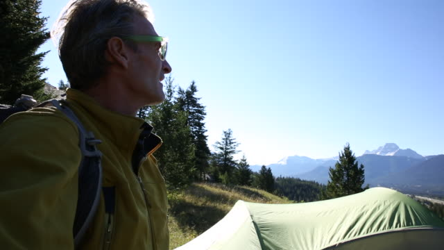 hiker pauses beside tent in mountain meadow - only mature men stock videos and b-roll footage