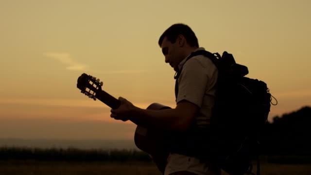 vídeos de stock, filmes e b-roll de caminhante tocando guitarra - violão