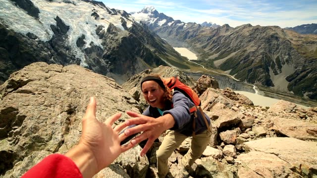 hiker pulls out his hand to get assistance from teammate - help single word stock videos and b-roll footage