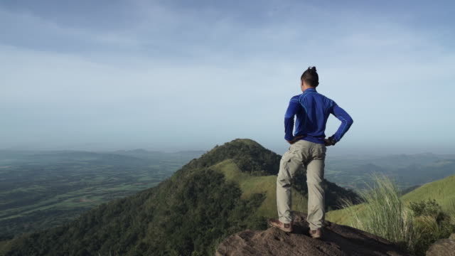 Hiker reaches a mountain summit and takes in the view