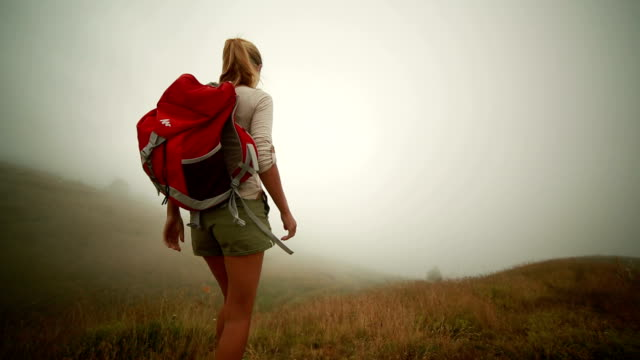 Hiker reaches foggy top, arms outstretched