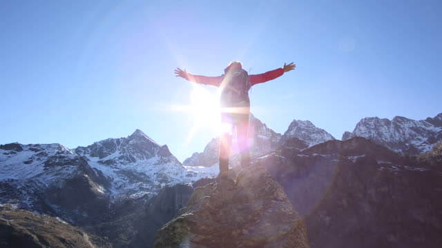hiker reaches pinnacle summit, spreads arms wide - arms outstretched stock videos and b-roll footage