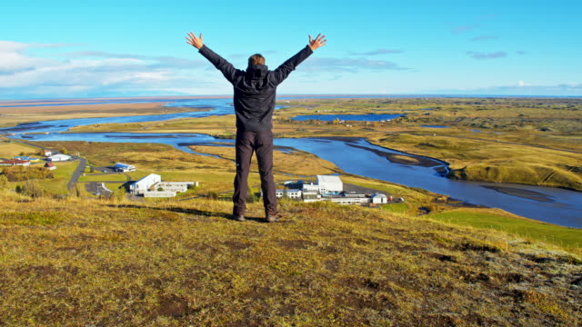 hiker rejoicing on hill above village - punching the air stock videos & royalty-free footage