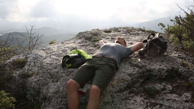 Hiker relaxes on stone ledge, above valley, distant hills