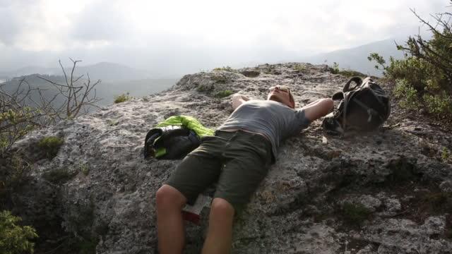 Wanderer entspannt auf Stein Felsvorsprung über dem Tal, fernen Hügel