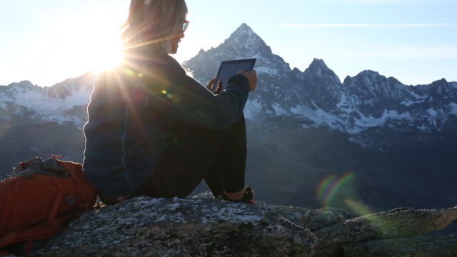 hiker relaxes on stone ridge, consults digital tablet for direction - rucksack stock videos and b-roll footage