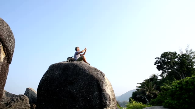 Hiker relaxes on top of jungle boulder, takes pic