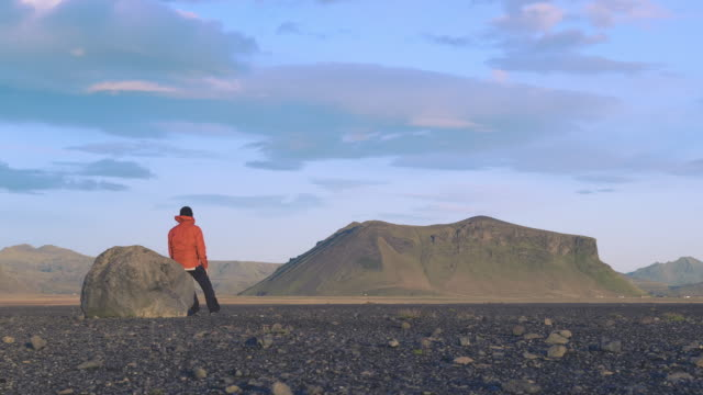 hiker resting on a rock on iceland - paesaggio spettacolare video stock e b–roll