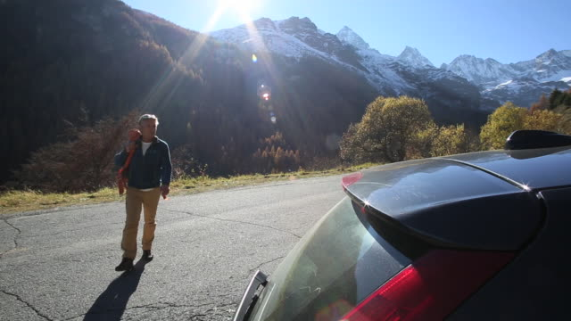 hiker returns to car by roadside, walking from mountains - only mature men stock videos & royalty-free footage