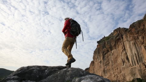 hiker scrambles across ridge crest, above hills and valley - valley stock videos & royalty-free footage