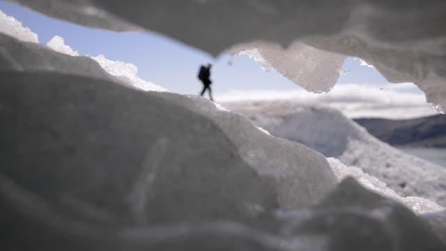 hiker seen through hole in icecap - icecap stock videos & royalty-free footage
