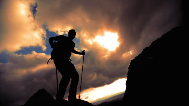 SLO MO hiker silhouette jumping on the ridge