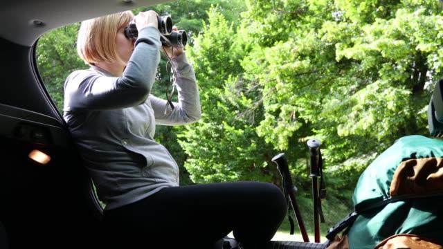 hiker siting on car trunk and using binoculars - attrezzatura sportiva video stock e b–roll