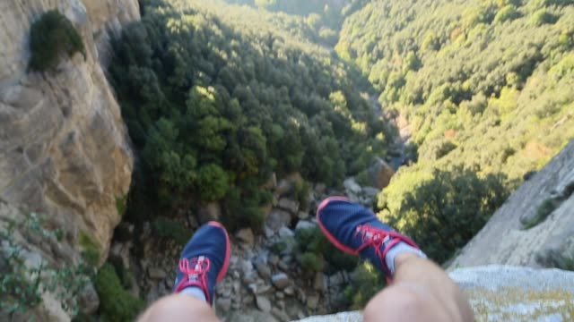 hiker sitting on cliff with the valley views from personal pov. - human leg stock videos & royalty-free footage