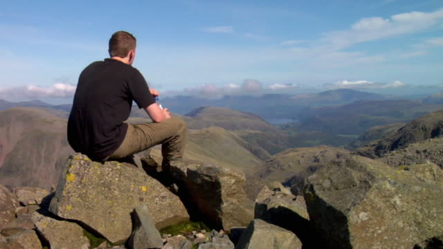 ws hiker sitting on rocks at top of mountain and drinking water / lake district, cumbria, uk  - english lake district stock videos and b-roll footage