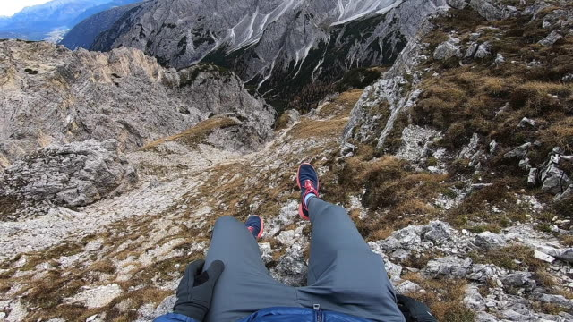 vidéos et rushes de hiker sitting on the edge with the sharp dolomite mountains in the italian alps from top of a hill. - vertige