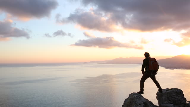 hiker spans gap between rocks above sea, sunset - horizont stock-videos und b-roll-filmmaterial