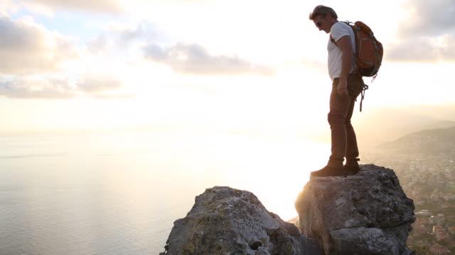 Hiker spans gap between rocks above sea, sunset