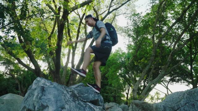 stockvideo's en b-roll-footage met wandelaar overspant kloof tussen rotsen, zonsondergang. - benen gespreid