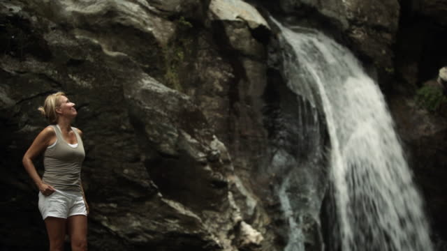 ws hiker standing next to a waterfall and looking around / stowe, vermont, united states - stowe vermont stock videos & royalty-free footage