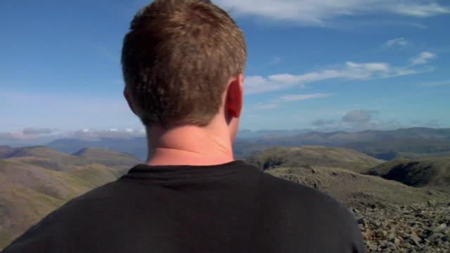 vídeos y material grabado en eventos de stock de cu pan hiker standing on top of mountain and looking at view / lake district, cumbria, uk  - distrito de los lagos de inglaterra