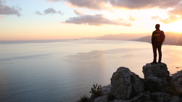 Hiker stands on rock bluff above sea, sunset